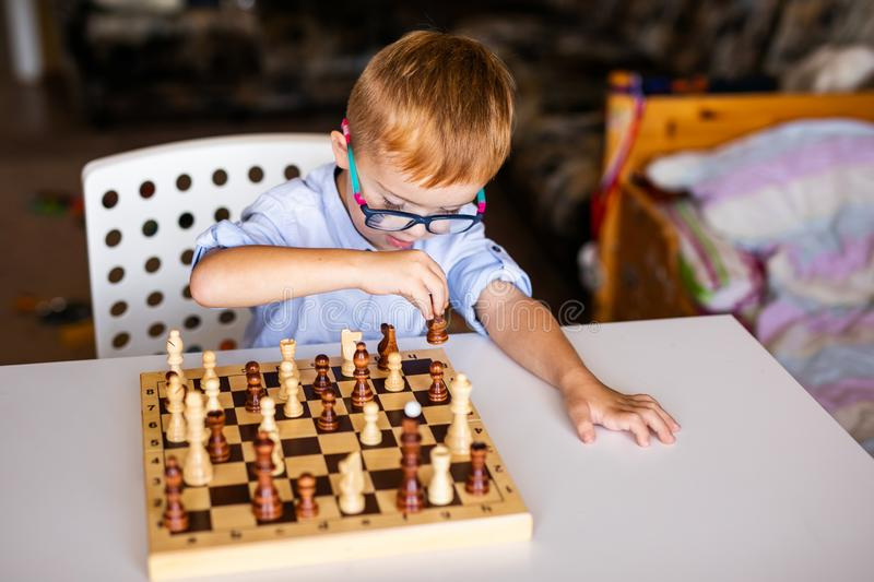 Little baby boy with down syndrome with big blue glasses playing chess in kindergarten.  royalty free stock photo