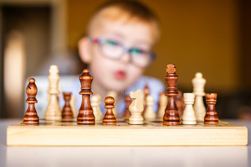 Little baby boy with down syndrome with big blue glasses playing chess in kindergarten.  royalty free stock image