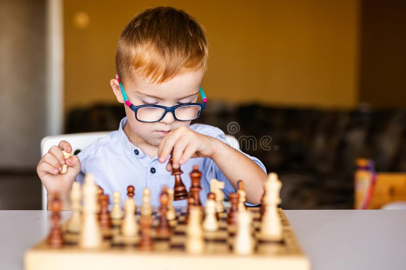 Little baby boy with down syndrome with big blue glasses playing chess in kindergarten.  royalty free stock images