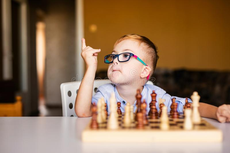 Little baby boy with down syndrome with big blue glasses playing chess in kindergarten.  stock photo