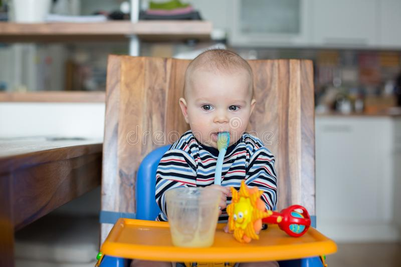Little baby boy, eating mashed food for the first time stock photography