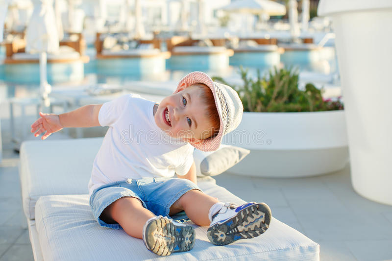 Little baby boy in a hat sitting on a background of the pool and royalty free stock photography