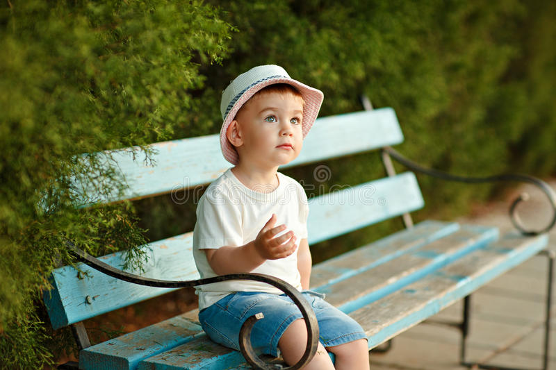Little baby boy in a hat sitting on a bench in the summer and lo stock photos