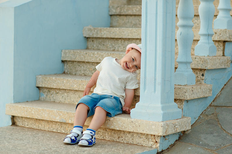 Little baby boy in the hat sitting on the steps of the house in royalty free stock photo