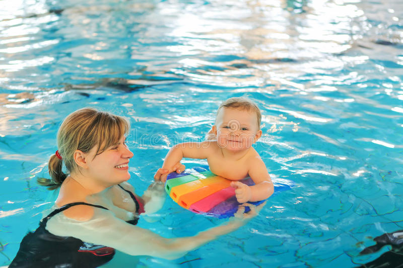 Little baby boy and his mother learning to swim in an indoor swimming pool. Having fun together. Baby swimming concept stock photo