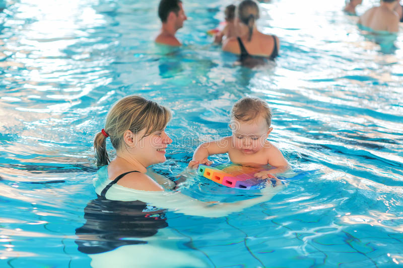 Little baby boy and his mother learning to swim in an indoor swimming pool. Having fun together. Baby swimming concept stock image