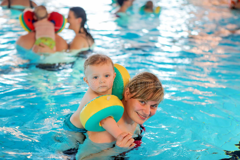 Little baby boy and his mother learning to swim in an indoor swimming pool. Having fun together. Baby swimming concept royalty free stock image