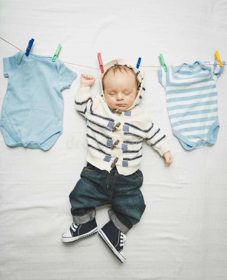 Little baby boy in jeans hanging on cord next to drying clothes stock image