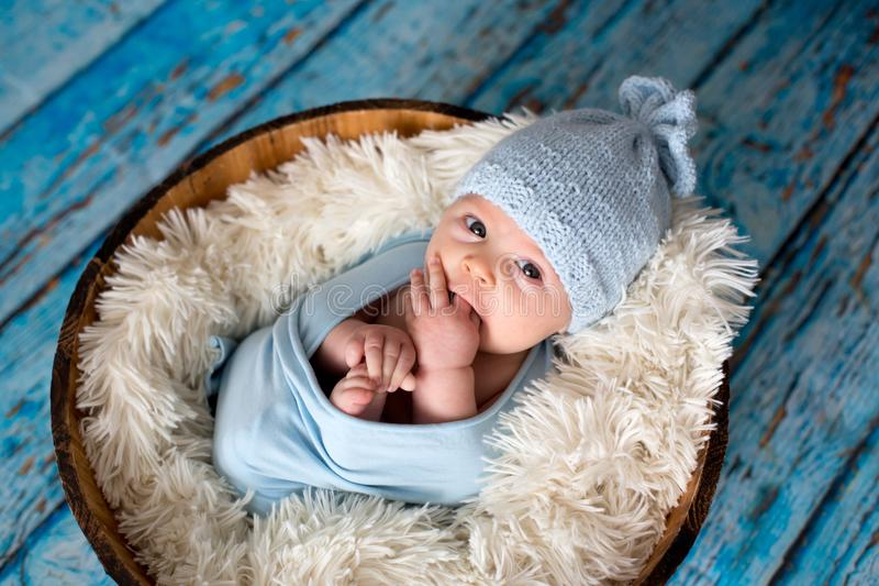 Little baby boy with knitted hat in a basket, happily smiling royalty free stock photography
