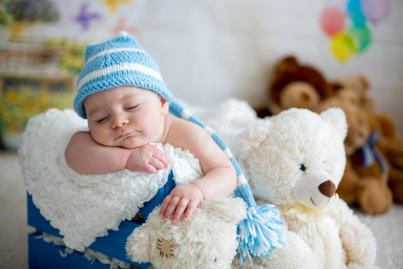 Little baby boy with knitted hat, sleeping with cute teddy bear stock photos