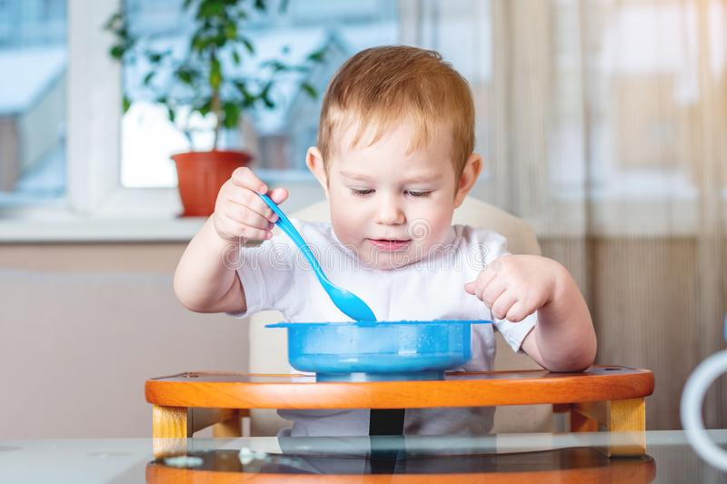 Little baby boy learning to eat with a spoon himself at the kids table in the kitchen. Concept of healthy baby food. Little baby boy learning to eat with a spoon stock photography