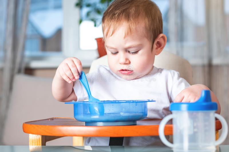 Little baby boy learning to eat with a spoon himself at the kids table in the kitchen. Concept of healthy baby food. Little baby boy learning to eat with a spoon royalty free stock photo