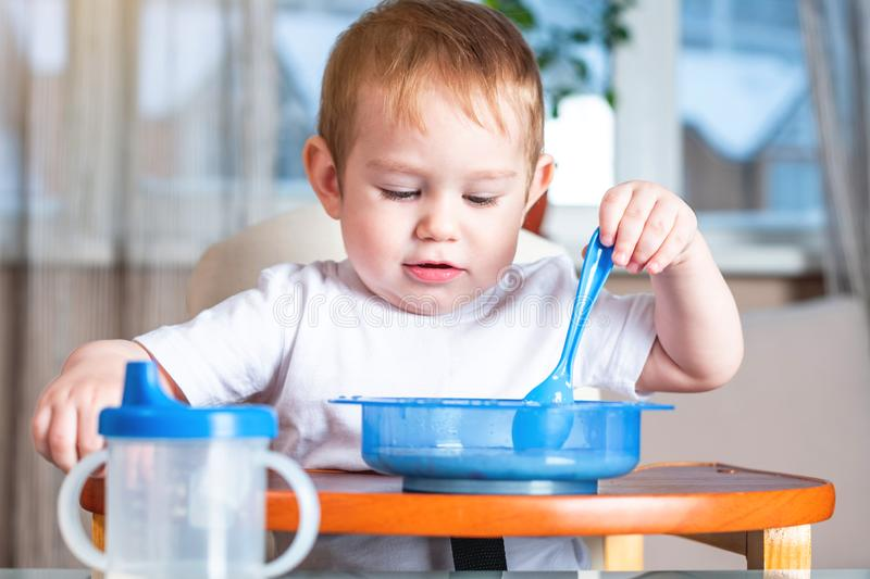Little baby boy learning to eat with a spoon himself at the kids table in the kitchen. Concept of healthy baby food. Little baby boy learning to eat with a spoon royalty free stock photography
