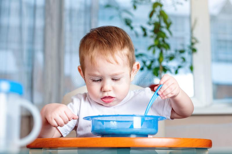 Little baby boy learning to eat with a spoon himself in the kitchen. Concept of healthy baby food. Little baby boy learning to eat with a spoon himself at the royalty free stock photos
