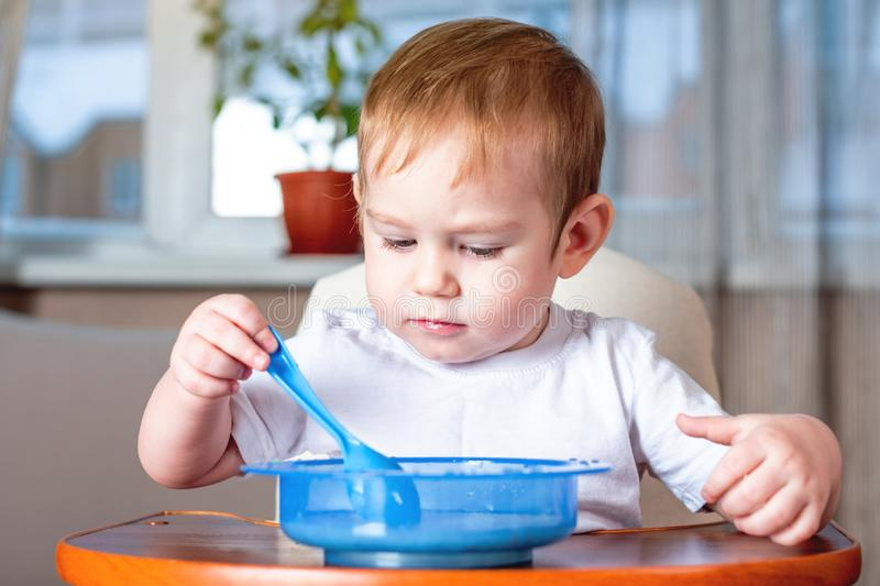 Little baby boy learning to eat with a spoon himself in the kitchen. Concept of healthy baby food. Little baby boy learning to eat with a spoon himself at the royalty free stock photo