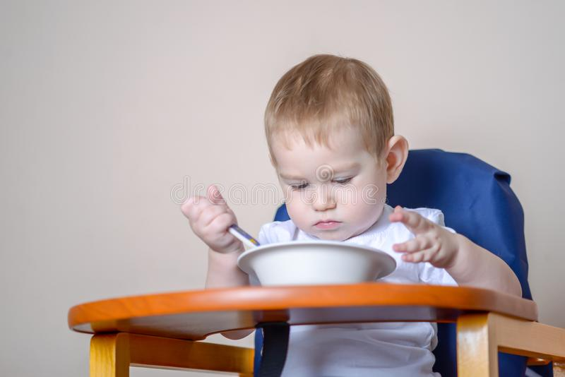Little baby boy learning to eat at a table studying a plate and spoon in the kitchen royalty free stock images