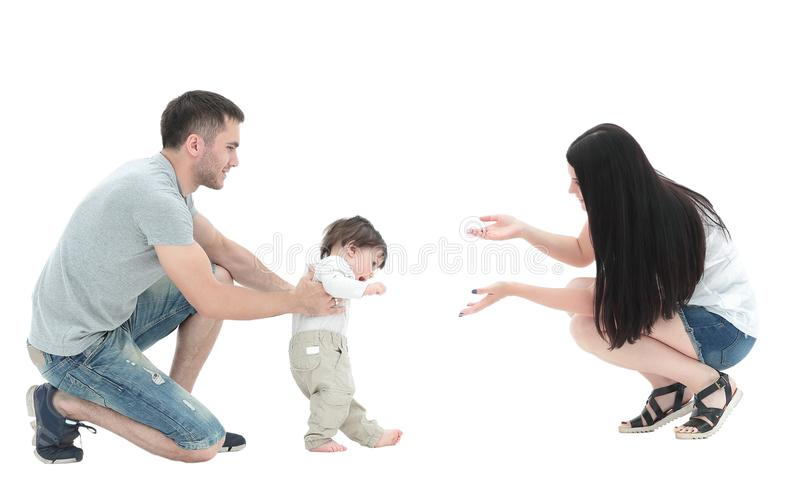 Little boy making first steps with the help of parents royalty free stock image