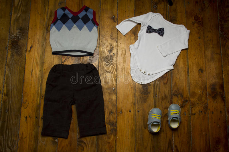 Little baby boy outfit for party on grunge wood background. Group of baby clothing: white onesie, shoes, trousers, vest and bow tie on grunge wooden background royalty free stock image
