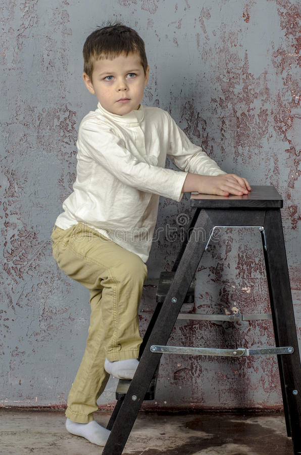 Little baby boy in plaid shorts and vest climb the ladder stock photos