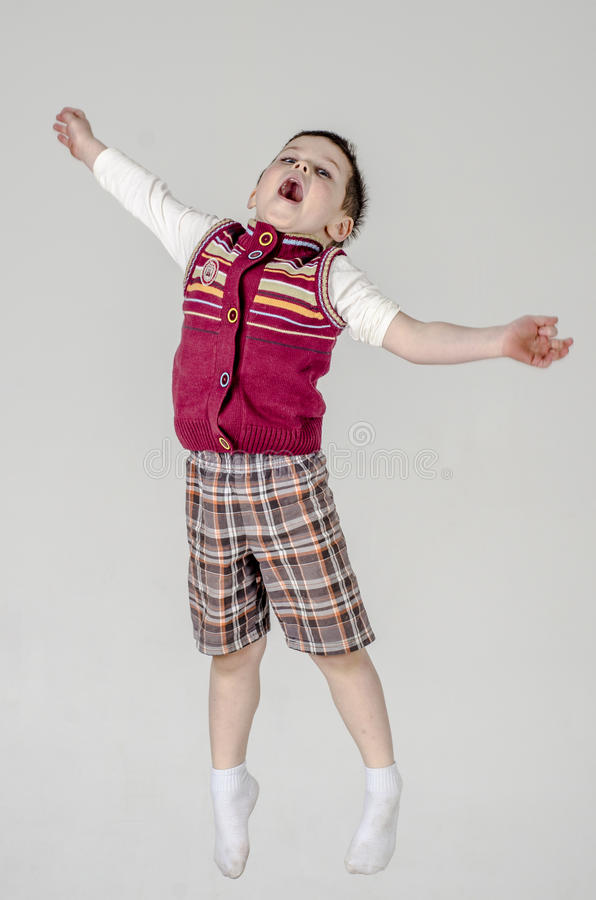 Little baby boy in plaid shorts and vest jumps royalty free stock photography