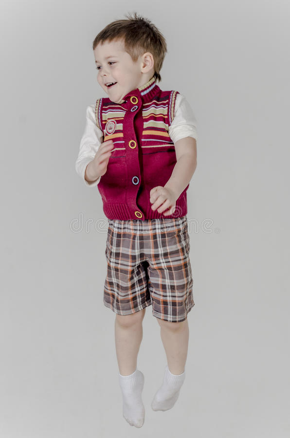 Little baby boy in plaid shorts and vest jumps royalty free stock image