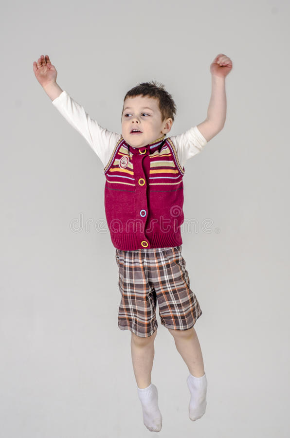 Little baby boy in plaid shorts and vest jumps stock photo