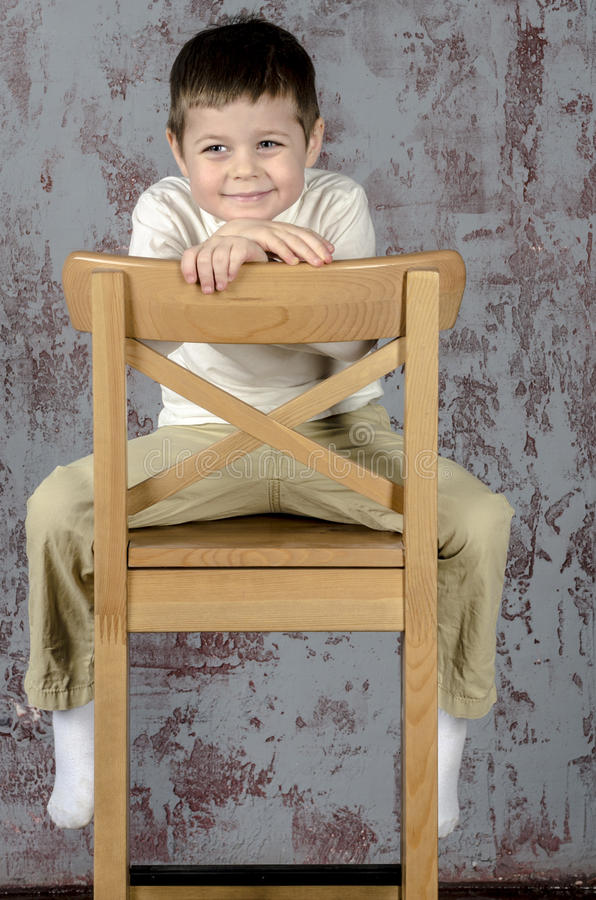 Little baby boy in plaid shorts and vest sitting on a chair stock image