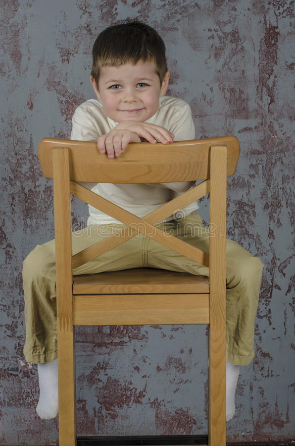 Little baby boy in plaid shorts and vest sitting on a chair royalty free stock photo