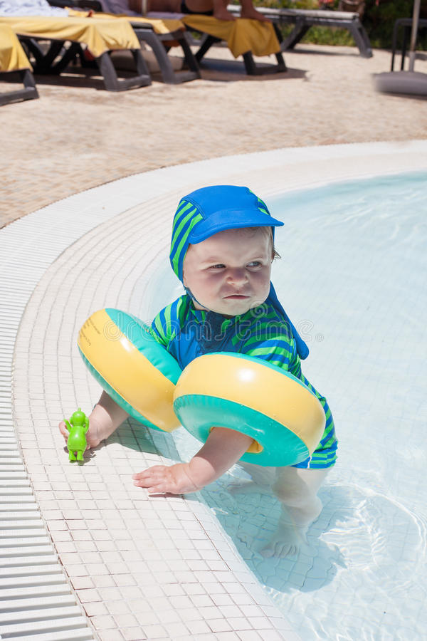 Little baby boy playing in the pool. With water. Outdoor, summer royalty free stock photography