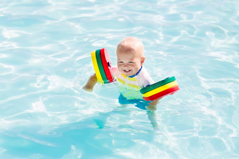 Little baby boy playing in swimming pool. Happy laughing little baby boy playing in outdoor swimming pool on a hot summer day. Kids learn to swim. Child with stock photo