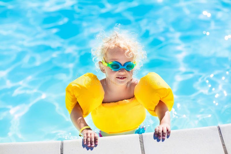 Little baby boy playing in swimming pool. Happy laughing little baby boy playing in outdoor swimming pool on a hot summer day. Kids learn to swim. Child with royalty free stock photos