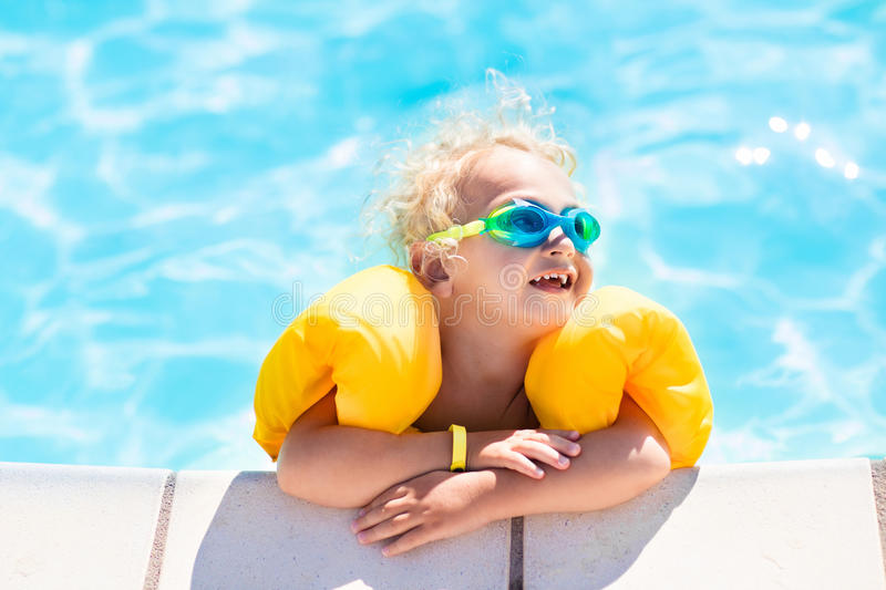 Little baby boy playing in swimming pool. Happy laughing little baby boy playing in outdoor swimming pool on a hot summer day. Kids learn to swim. Child with royalty free stock photo