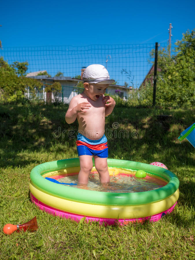 Little baby boy playing in swimming pool stock photography