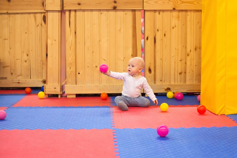 Little baby boy plays with colorful balls in playground. Ball pit at kids play center stock photos