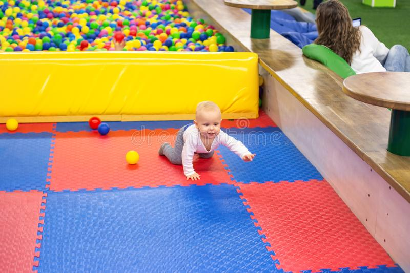 Little baby boy plays with colorful balls in playground. Ball pit at kids play room. Baby crawling on a soft rug stock photography