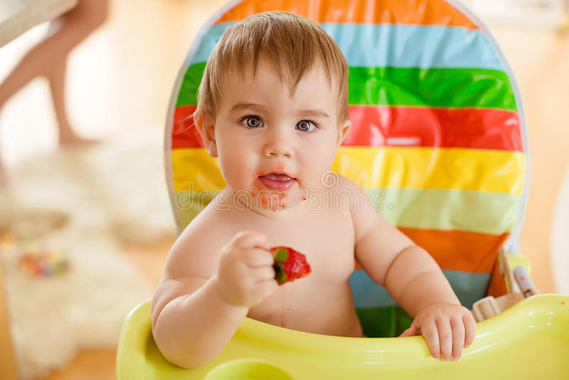Little baby boy sitting in a bright chair, eating strawberries royalty free stock photos