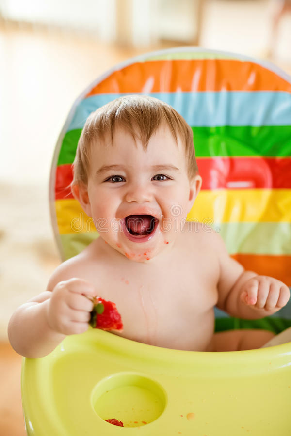 Little baby boy sitting in a bright chair, eating strawberries a royalty free stock images