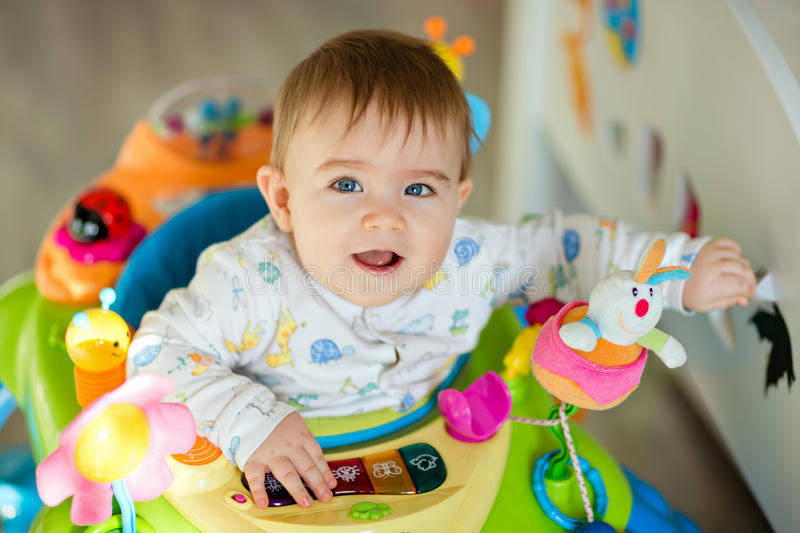 Little baby boy sitting in a colourful baby Walker with toys and royalty free stock photo