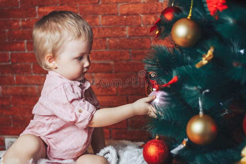 Baby touching chistmas toys on christmas tree, he try to put ball on the tree. Little baby boy is sitting on floor under Christmas tree and reaching for toy on royalty free stock images