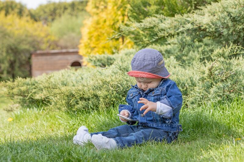 Little baby boy sitting outdoors is using smart phone royalty free stock images