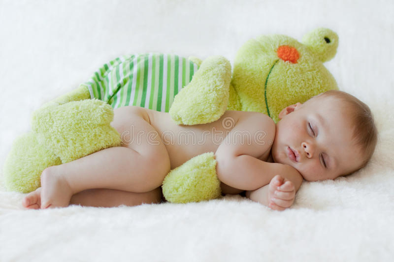 Little baby boy, sleeping with big teddy frog stock photos