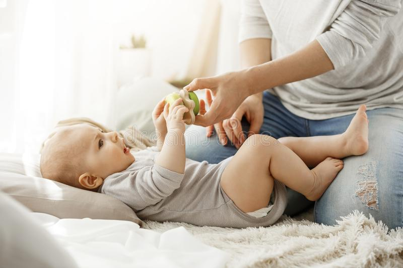 Little baby boy spending happy childhood with young mother. Child trying to take a beautiful toy from tender mom hands royalty free stock photography