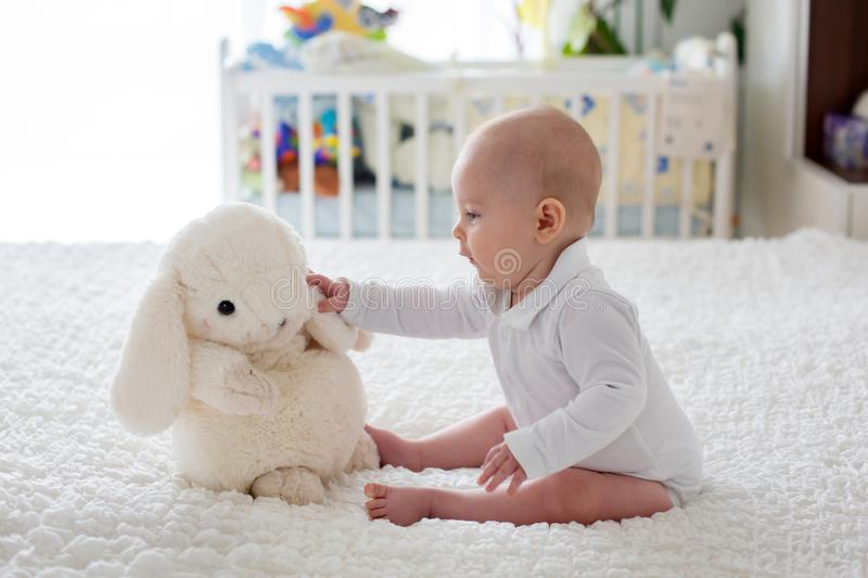 Little baby boy, toddler, playing at home with plush toy in bed stock image