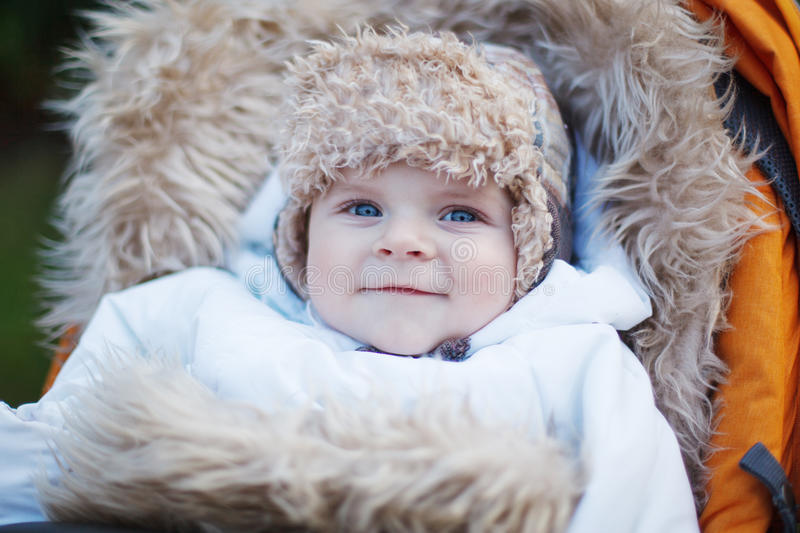 Little baby boy in warm winter clothes outdoor. Little baby boy in warm winter clothes and orange pram outdoor royalty free stock photography