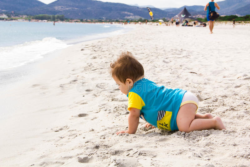 Little baby boy wearing blue rash guard suit playing on tropical ocean beach. UV and sun protection for young children. Toddler ki. D during family sea vacation stock photo