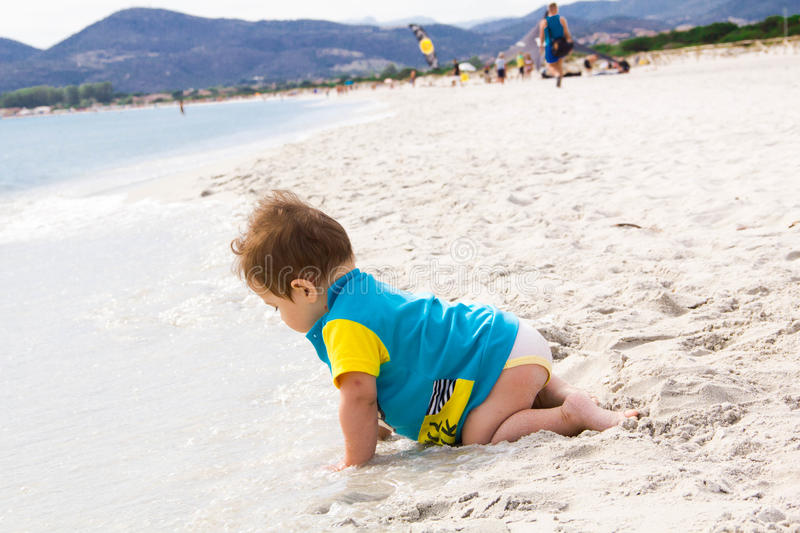 Little baby boy wearing blue rash guard suit playing on tropical ocean beach. UV and sun protection for young children. Toddler ki. D during family sea vacation stock image