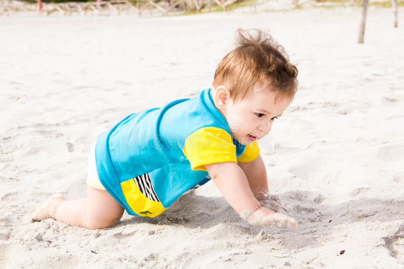 Little baby boy wearing blue rash guard suit playing on tropical ocean beach. UV and sun protection for young children. Toddler ki. D during family sea vacation royalty free stock image