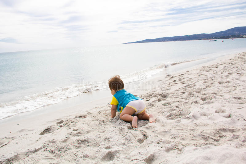 Little baby boy wearing blue rash guard suit playing on tropical ocean beach. UV and sun protection for young children. Toddler ki. D during family sea vacation royalty free stock images