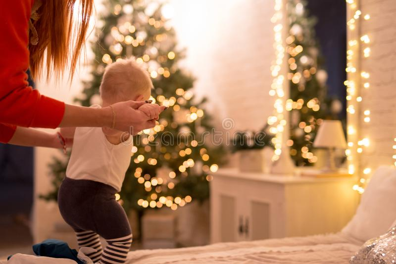 Little baby boy 1 year old learning how to walk in a decorated New Year house. Mom hold by the hands of her son. stock images