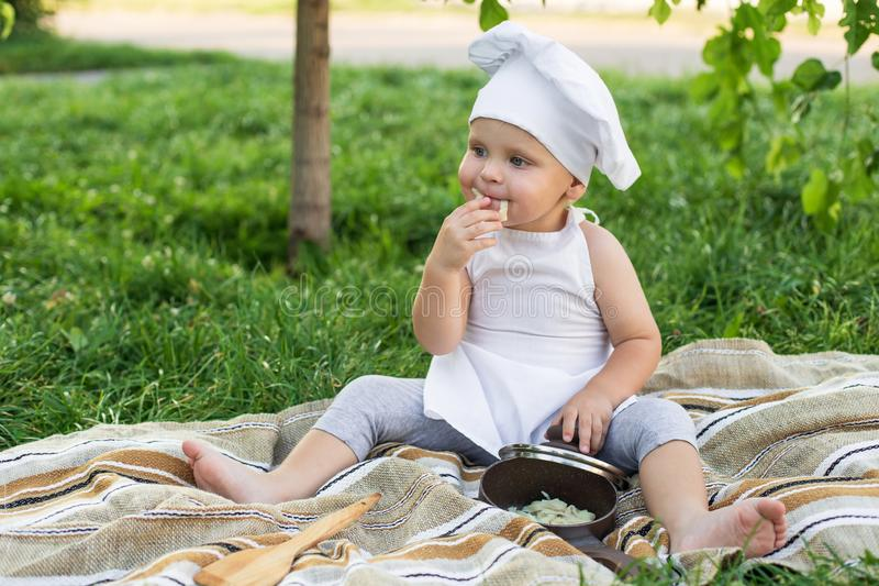 Little baby chef cooks lunch on a picnic outdoors. Cute child in a cook suit with pan and cooking spatula on the green nature royalty free stock images